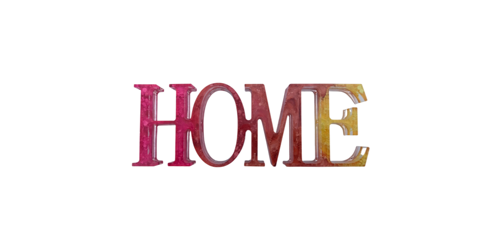 """Pink, red, orange and yellow resin sign which reads """"HOME"""""""