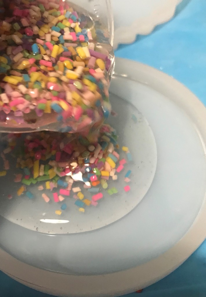Pouring polymer clay sprinkles mixed with clear resin into a coaster mould