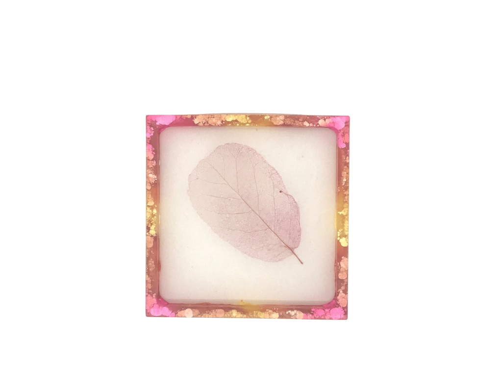 Square coaster with magenta, orange and yellow alcohol ink with dried flower in the centre